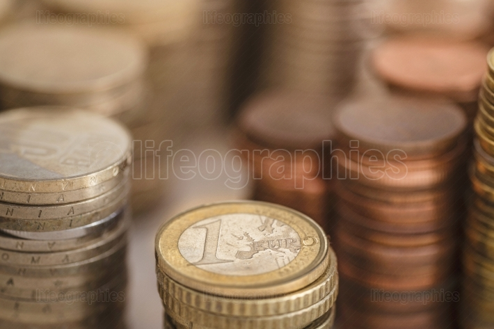 1 (one) euro coin between other currencies with gold background