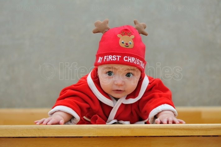 A baby in a santa suit