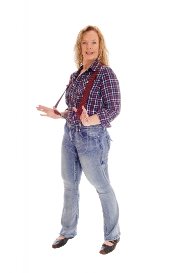 A blond woman standing in jeans and suspender.