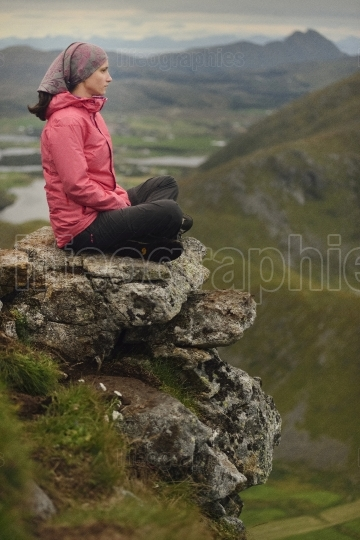 A Female hiker having a rest after climbing a mountain, Lofoten Islands, Norway