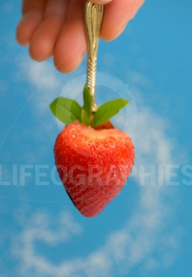 A heart shaped strawberry in spoon