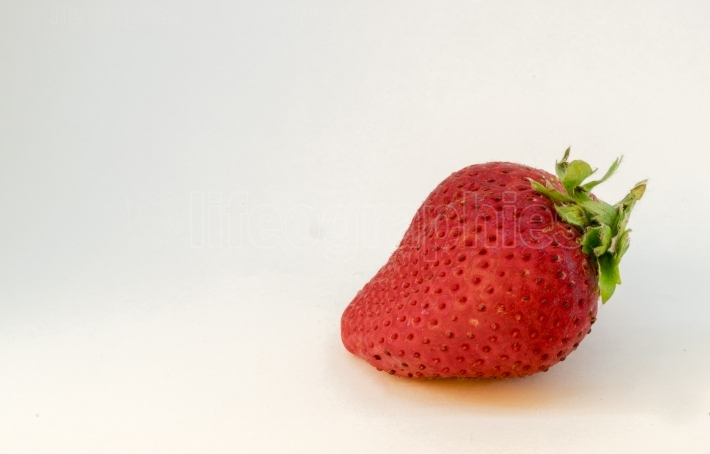 A perfectly cleaned strawberry with leaves isolated on the white