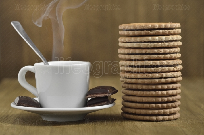 A wooden table with cup of coffee and chocolate pieces cookies biscuits filled with chocolate.