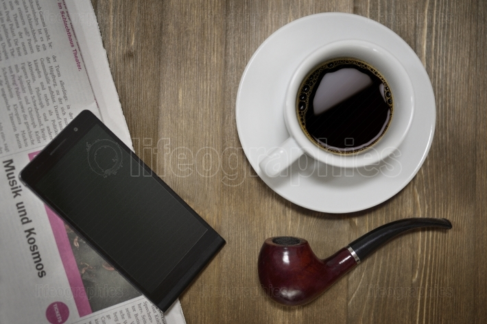 A wooden table with newspaper, smart phone, tobacco pipe and a cup of coffee.