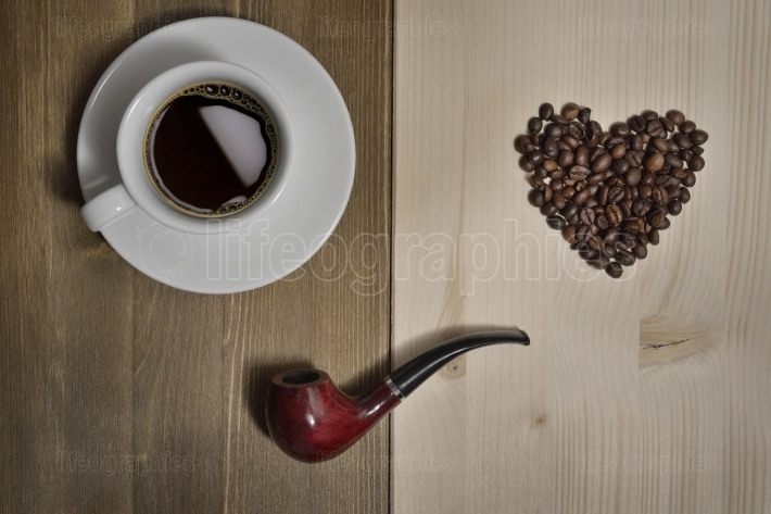A wooden table with tobacco pipe, a cup of coffee and a heart made by coffee beans.