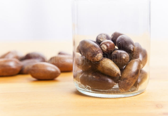 Acorns on glass jar over wooden surface