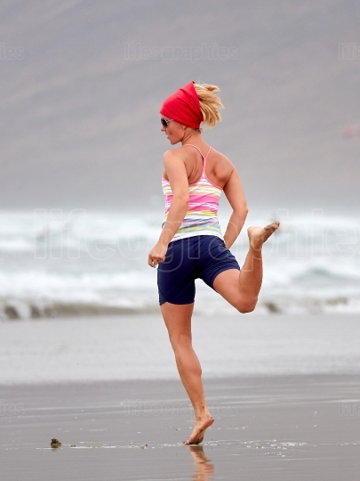 Active sporty woman on the beach in summer morning