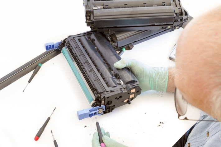 Adult man working toner cartridge