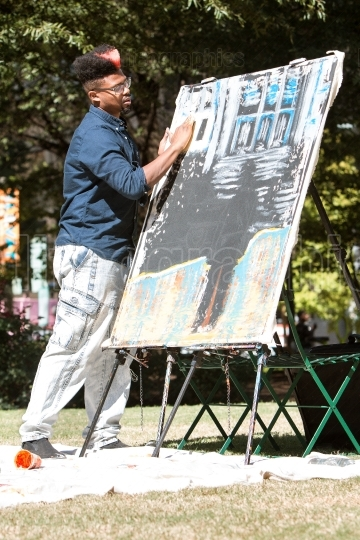 African american artist paints with his fingers at arts festival