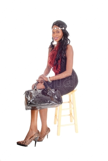 African American woman sitting on chair.