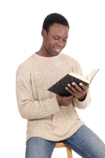 African man sitting and reading his book