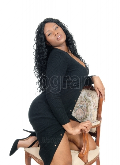 African woman kneeling on chair.