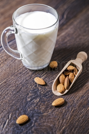 Almond milk and nuts over rustic wooden background