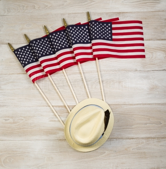 American Flags and Hat with feather on faded white wooden boards
