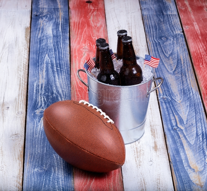 American football and ice cold beer on rustic wooden boards