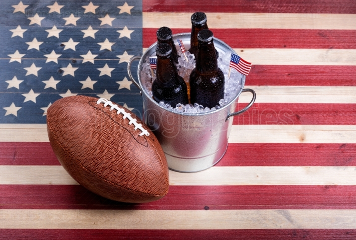 American football and ice cold beer on rustic wooden USA flag