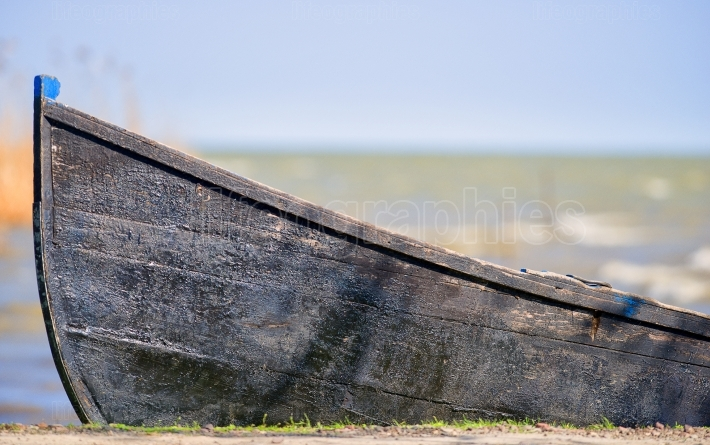 An old wooden boat turned upside down on the green grass