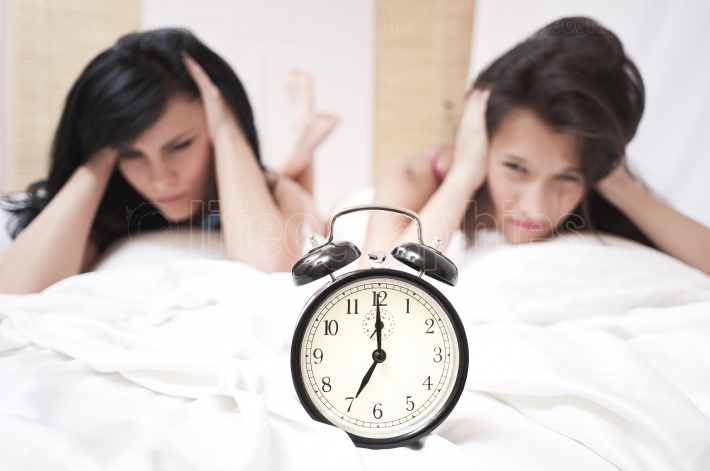 Angry sleeping women looking at a ringing clock