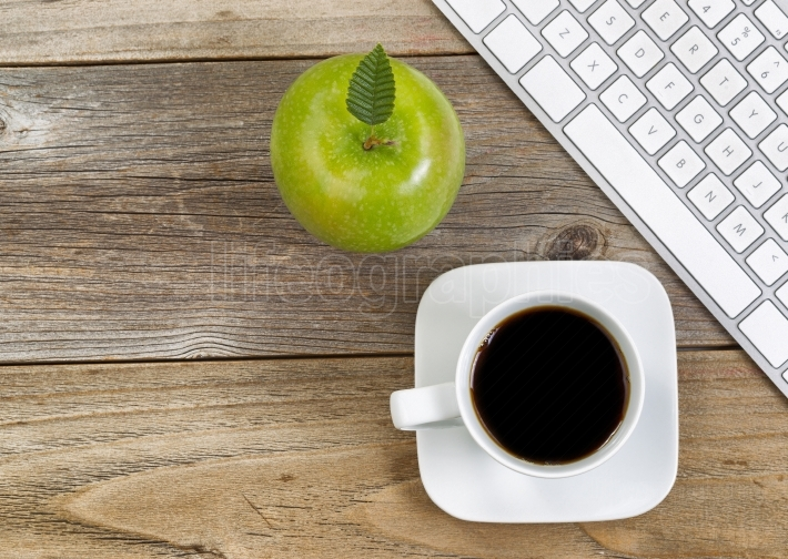 Apple and black coffee with computer keyboard for school or offi