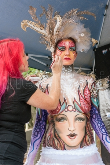 Artist applies colorful body paint to female model at festival