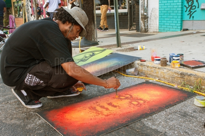 Artist flicks yellow paint onto painting at arts festival