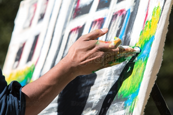 Artist paints canvas with his fingers at atlanta arts festival