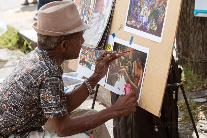 Artist paints scene on paper at eclectic arts festival