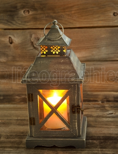 Asian Lantern and glowing white candle inside on weathered wood