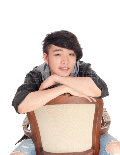 Asian man sitting backwards on chair