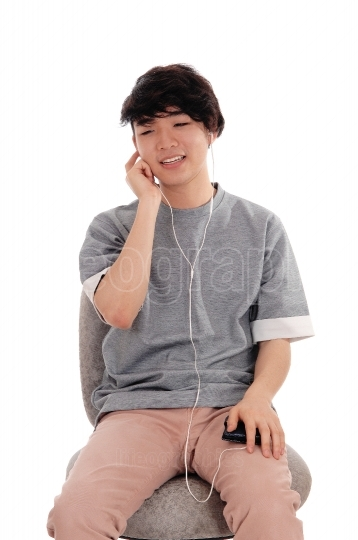 Asian teenager listening to music.