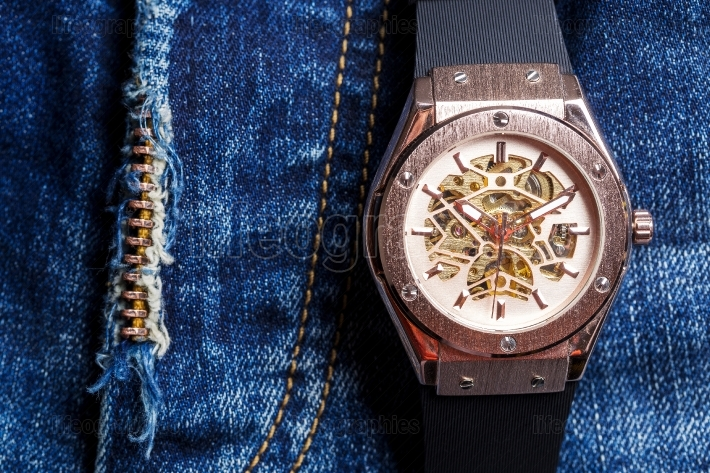 Automatic men watch with visible mechanism on blue jeans backgro