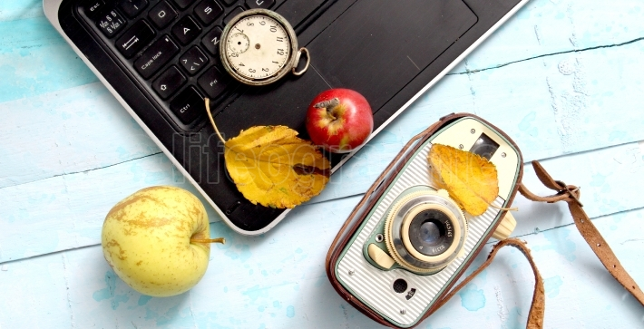 Autumn concept, ripe apples, laptop,leaves on blue paint wood surface,top view
