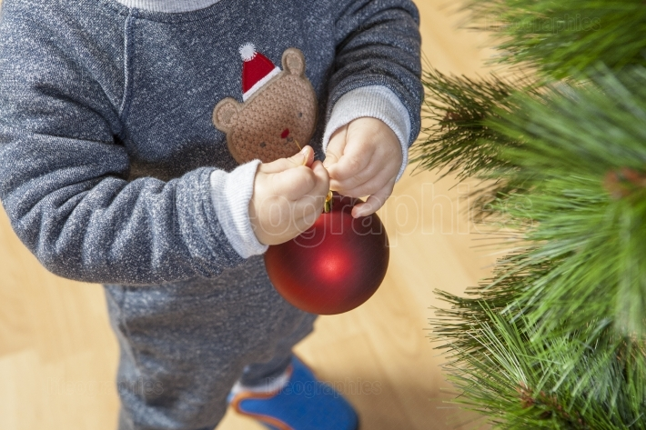 Baby boy decorates Xmas Tree with red ball