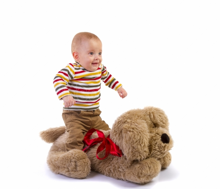 Baby boy jumping over plush dog