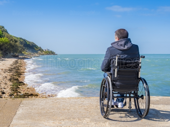 Back of disabled man in wheelchair at beach