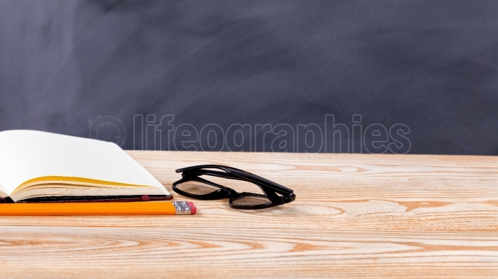 Back to school basic objects in front of erased black chalkboard