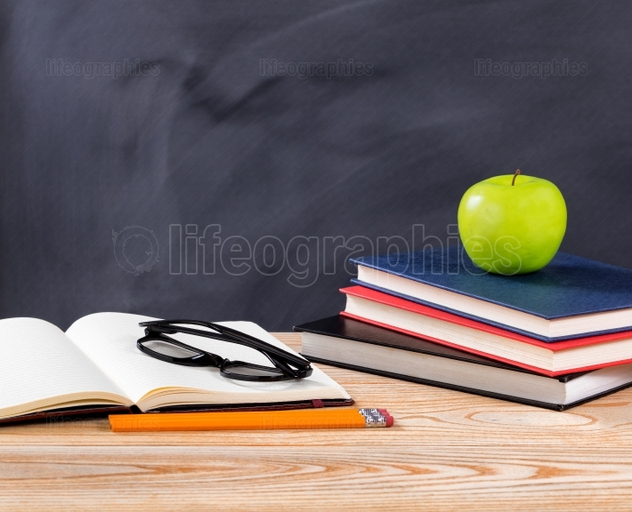 Back to school desk with stationery objects in front of erased b