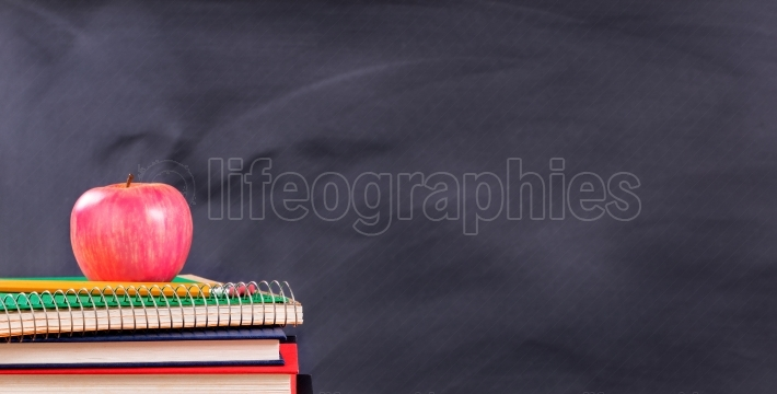 Back to school materials in front of black chalkboard