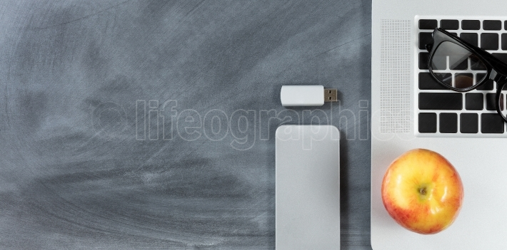Back to school modern technology objects on erased chalkboard