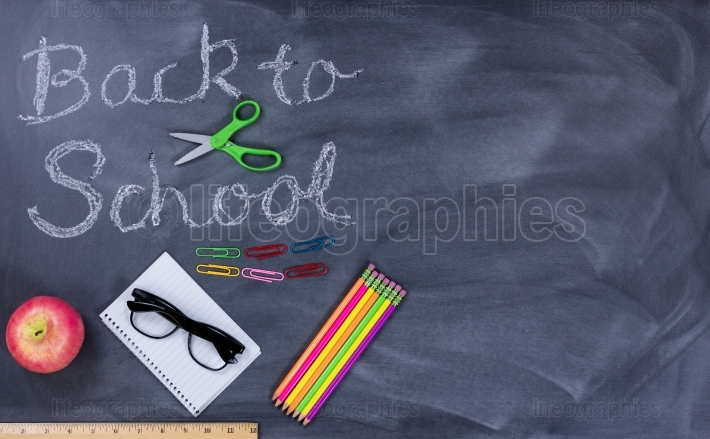 Back to school text on erased chalkboard with student supplies
