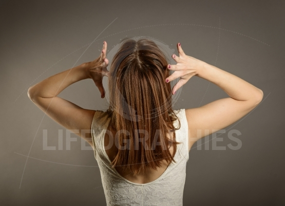 Back view of woman with hands on head