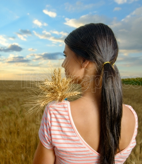 Back view on young woman in wheat field at sunset . Lifestyle and happiness concept