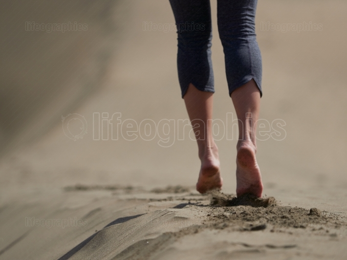Bare feet of young woman jogging walking on the beach at sunrise