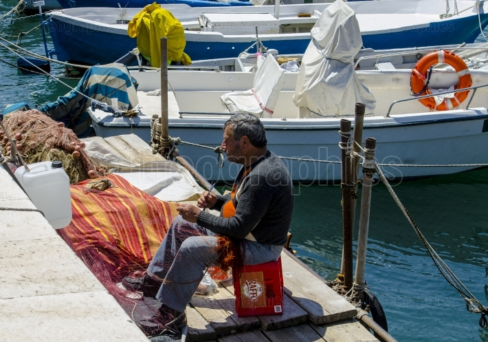 Bari, Italy   May 30, 2014  Old fisherman repairs his fishing nets on the quay of the port of Bari