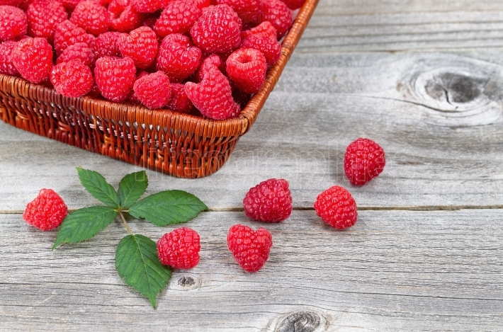 Basket Filled with Fresh Ripe Raspberries on Aged Wood
