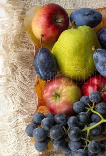 Basket full of fruits. Pear, apple, grape and plum