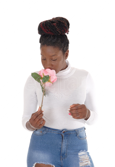 Beautiful African woman standing smelling a pink rose