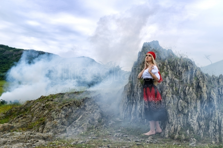 Beautiful blonde woman in old-fashioned dress surrounded by smoke