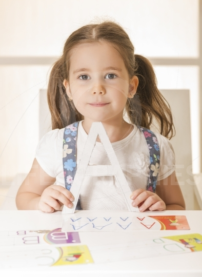 Beautiful expressive little girl posing with letter A