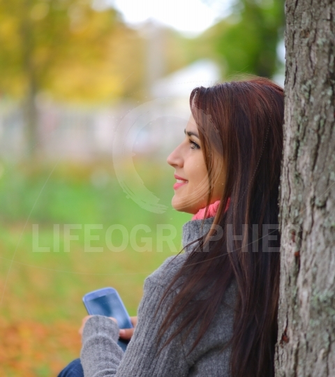 Beautiful girl messaging with phone in autumn park